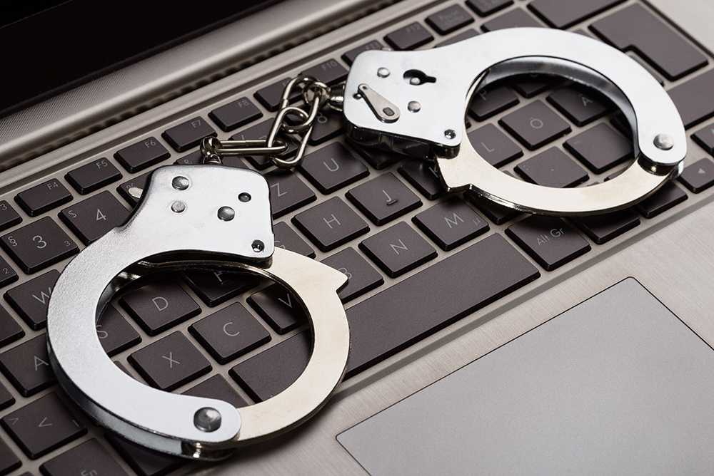 Photo Of Handcuffs Lying On Laptop Keypad